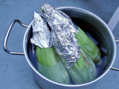 Soaking corn before grilling.
